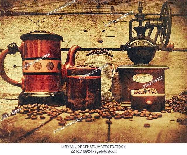 Cafe background on coffee bean grinder beside old ceramic pot, bag, mug and loose kernels on wooden background