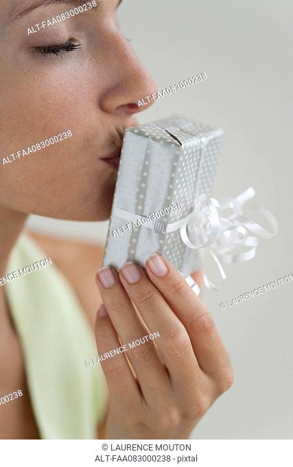 Young woman kissing gift, eyes closed, side view