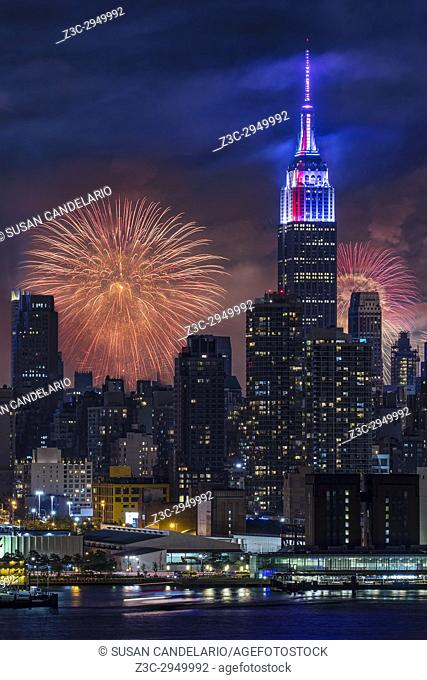 NYC Fourth Of July Fireworks - New York City skyline with the Macy's Spectacular 4th of July Fireworks Celebration Show as a backdrop to midtown Manhattan