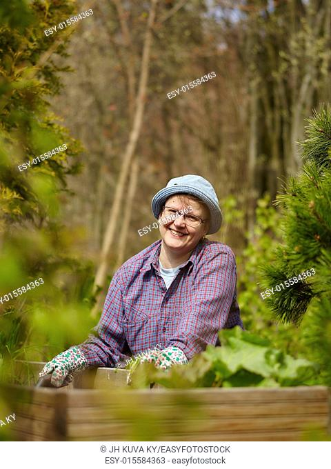 Woman weeding in the garden and she use protective gloves