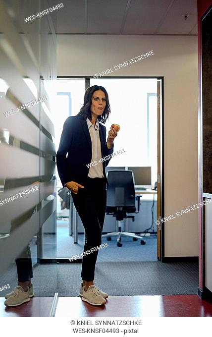 Mature businesswoman standing in office corridor, eating apple