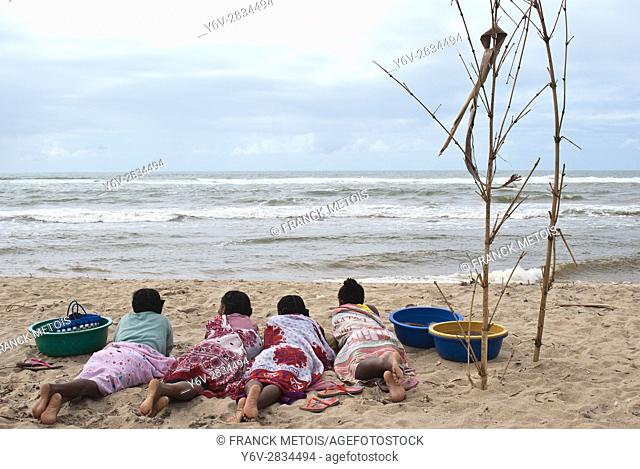 Women are lying on a beach. They are waiting for the return of fishermen to collect fishes before going to the market to sell them