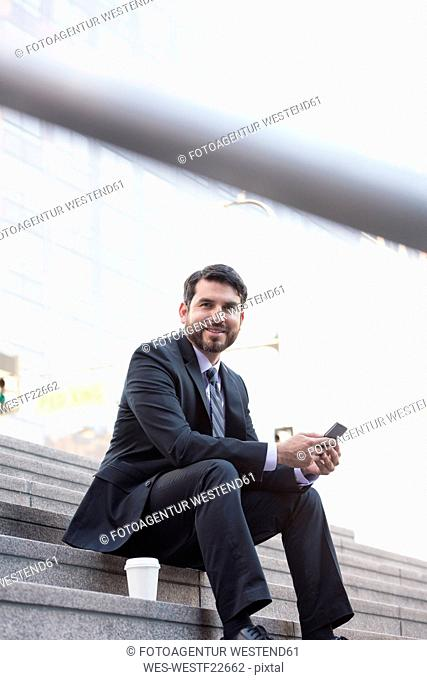 Smiling businessman sitting on stairs with cell phone and takeaway coffee