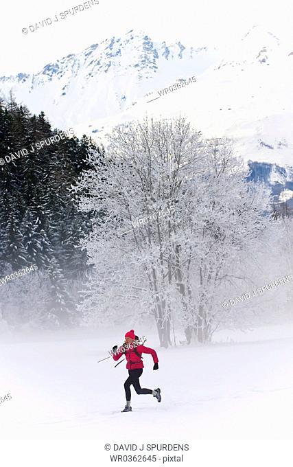 Women running across snowy field