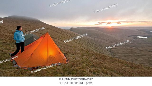 Hiker at campsite overlooking landscape