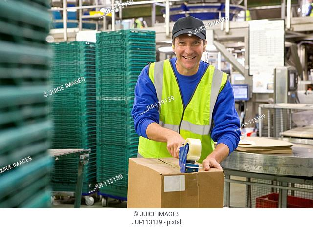 Portrait confident worker taping box in food processing plant