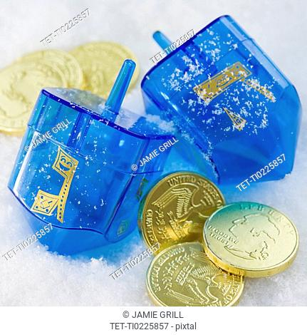 Close up of Chanukah coins and dreidels in snow