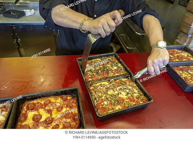 A pizza chef removes a mushroom topped Detroit style deep dish pizza from its pan at the newly opened Lions & Tigers & Squares pizzeria in Chelsea in New York...