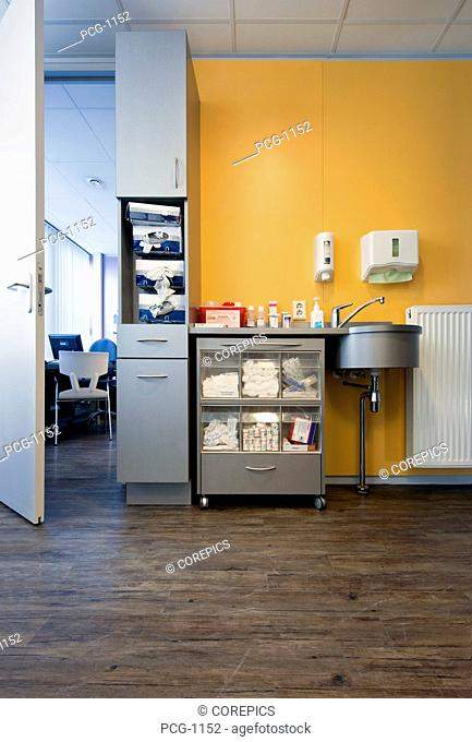 A city drop-in or emergency medical centre. A treatment room with equipment for a medical examination and treatment. Medical supplies in storage chests