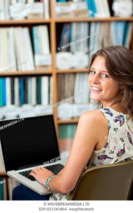 Smiling female student against bookshelf using laptop in library