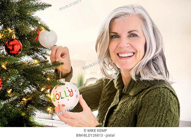 Portrait of Caucasian woman hanging ornaments on Christmas tree