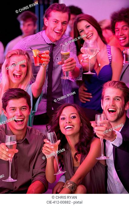 Portrait of smiling friends drinking cocktails in nightclub