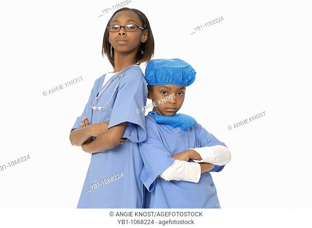 Two girls, ten and six years old, dressed as doctors
