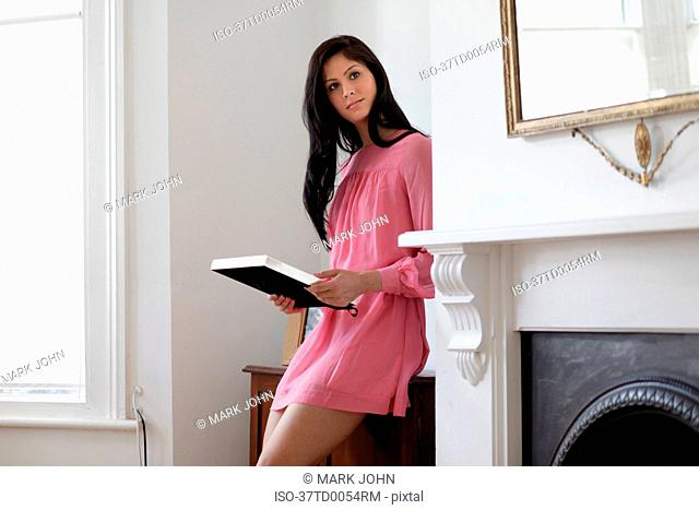 Woman holding book in living room