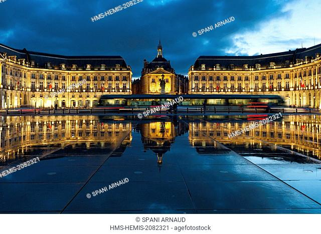 France, Gironde, Bordeaux, area listed as World Heritage by UNESCO, Bourse Place, La Lune harbour, Night view of a tram passing a historic building and their...