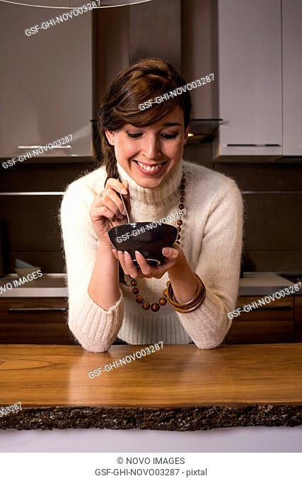 Smiling Woman Holding Brown Bowl in Kitchen