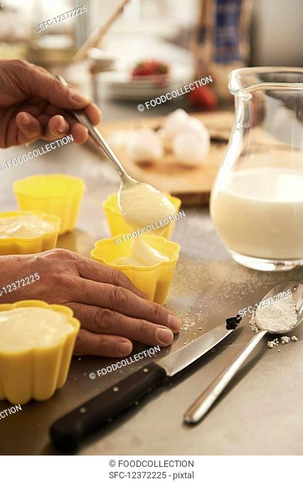 Molds being carefully filled with pudding