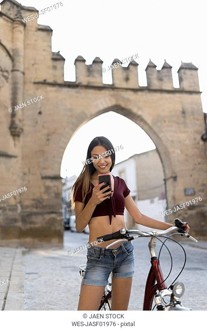 Spain, Baeza, portrait of smiling young woman with bicycle looking at cell phone