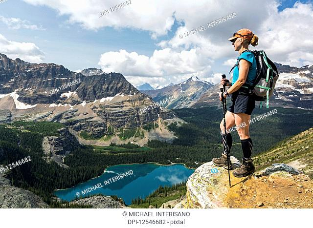 Female hiker standing on cliff edge overlooking mountains and valley with colourful alpine lake; British Columbia, Canada