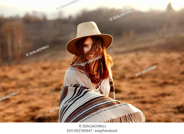 beautiful boho woman hipster, smiling and having fun at sunset in mountains, wearing hat and poncho
