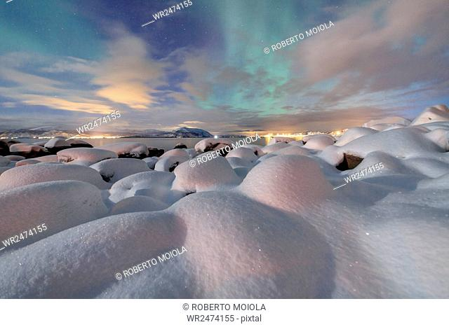 The pink light and the aurora borealis (Northern Lights) illuminate the snowy landscape on a starry night Stronstad, Lofoten Islands, Arctic, Norway Scandinavia
