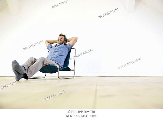 Man sitting in arm chair, daydreaming