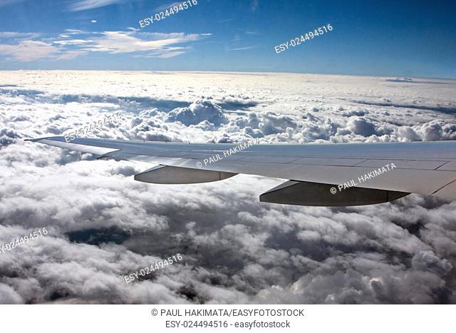 Airplane wing flying above white clouds