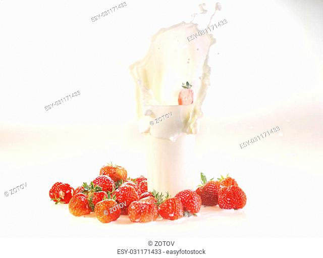 Milk splash in a glass, milk and a strawberry on a white background
