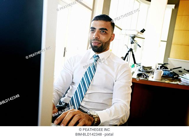 Middle Eastern businessman working at computer in office