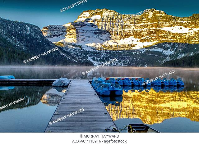 Cameron Lake in the early morning light showing wooden pier and canoe, with mountain reflections in lake. Waterton National Park, Alberta, Canada