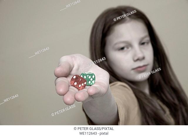Preteen girl holding colored dice