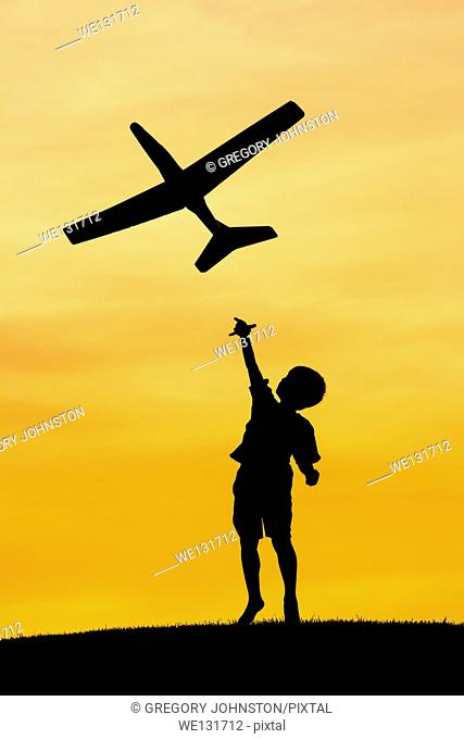 A young boy flies a toy plane during a bright orange sunset