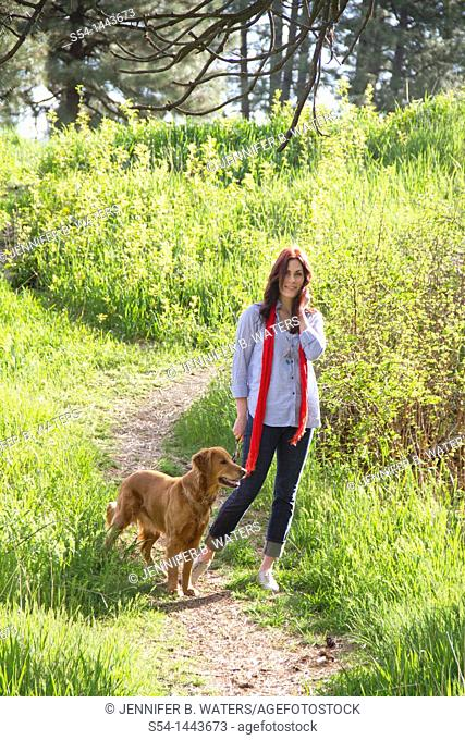 A woman outdoors with her Golden Retriever