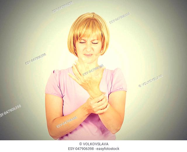 Close-up portrait Young woman holding her painful wrist isolated on background. Sprain pain, armache