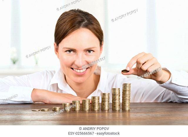 Close-up Of Happy Businesswoman Placing Coin To Stack Of Coins