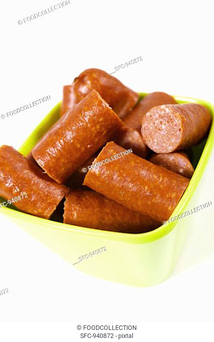 Pieces of Debreziner sausage in plastic bowl