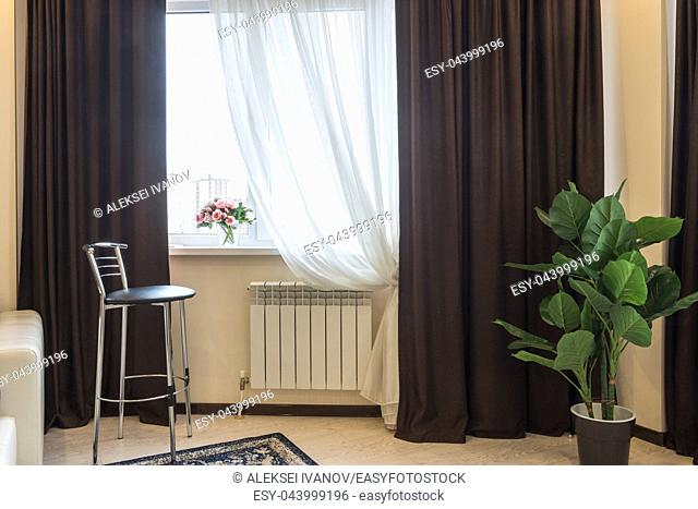 Interior element, bar stool, curtain windows, vase with flowers on the window
