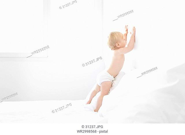 Baby boy with blond hair leaning on a bed with white duvet and pillows, touching wall