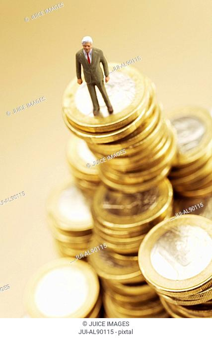 Businessman figurine on stack of Euro coins