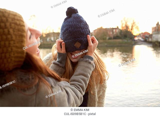 Young woman putting knitted hat on friend, hat covering eyes, laughing