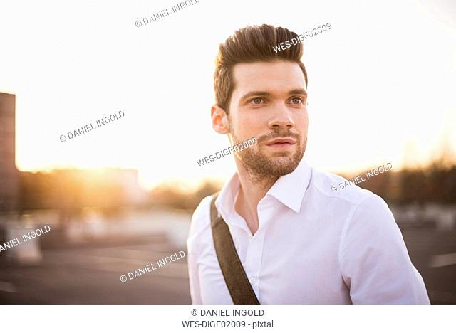 Portrait of young businessman at sunset