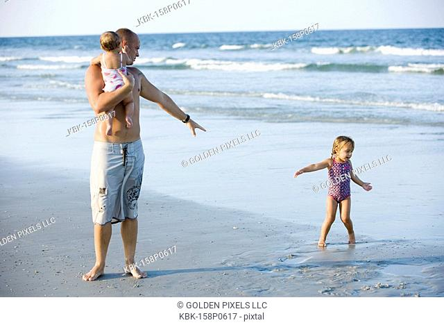 Father with young daughters at the beach