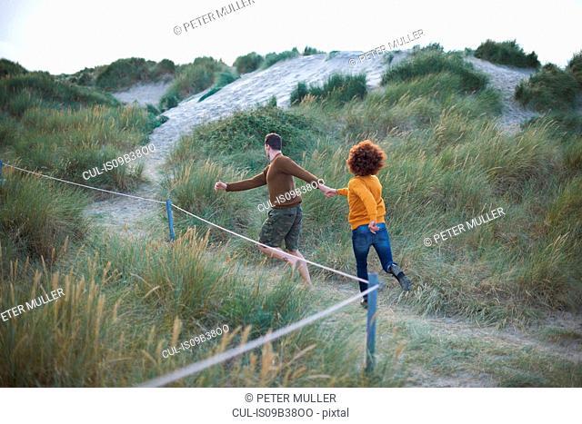 Couple running on grassy dune