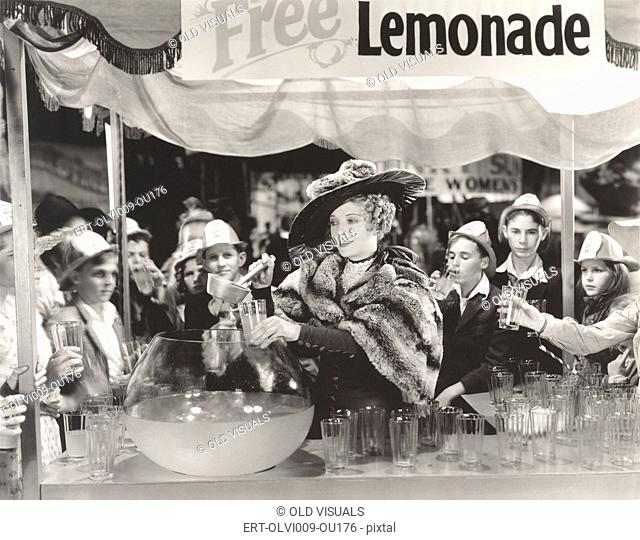 Woman giving out free lemonade to children at fair