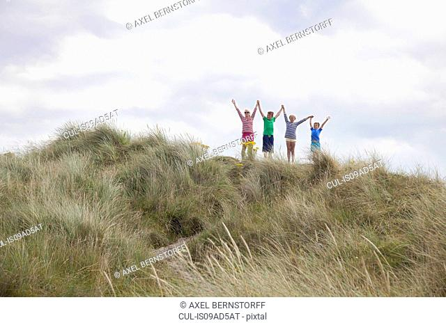 Four friends on dunes with arms out, Wales, UK