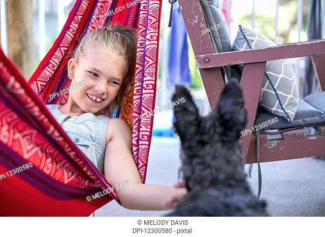 Girl relaxing in a hammock and petting her dog; Langley, British Columbia, Canada