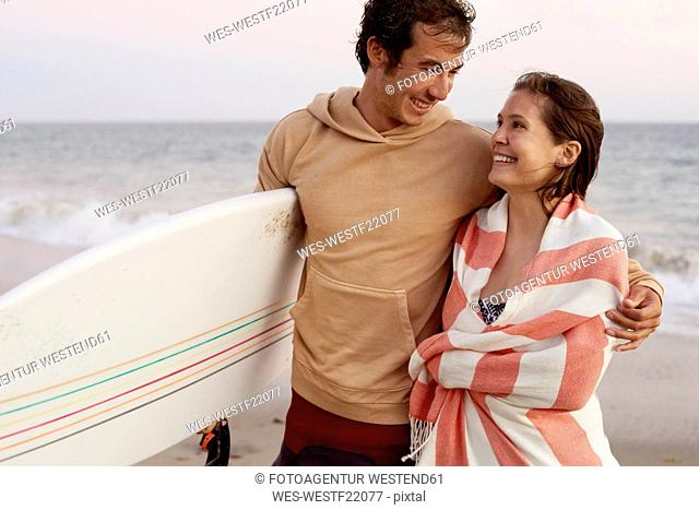 Smiling young couple on the beach carrying surfboard