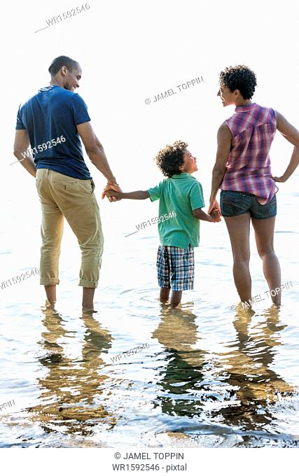 A family, mother, father and son playing on the shores of a lake