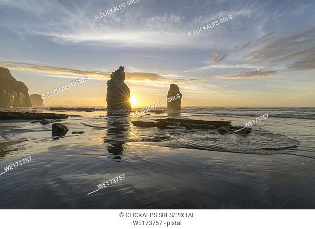 The sun in setting down behind the Three Sisters. Tongaporutu, New Plymouth district. Taranaki region, North Island, New Zealand