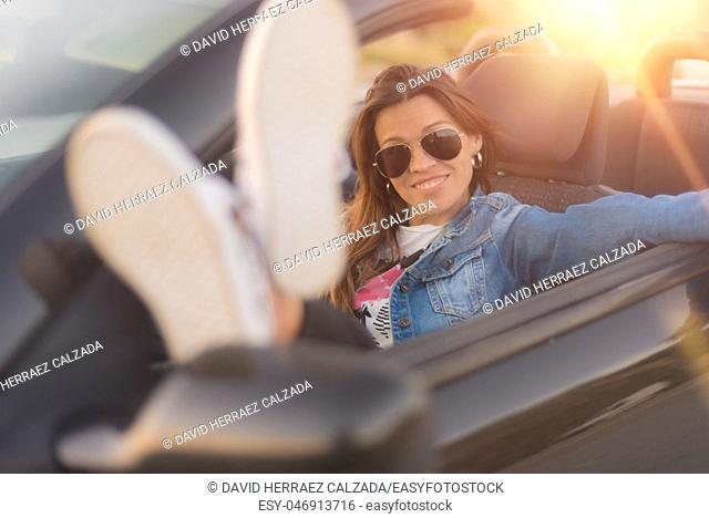 Happy young woman enjoying her convertible car